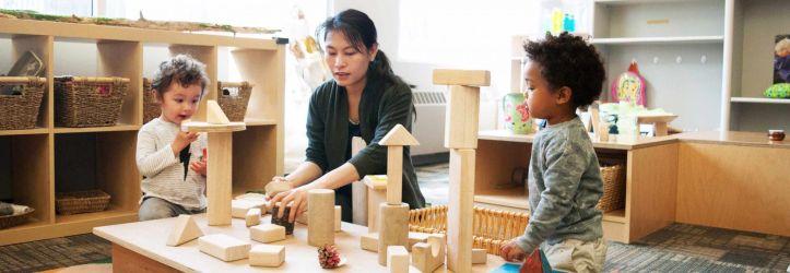 child-care-professional-building-blocks-with-children